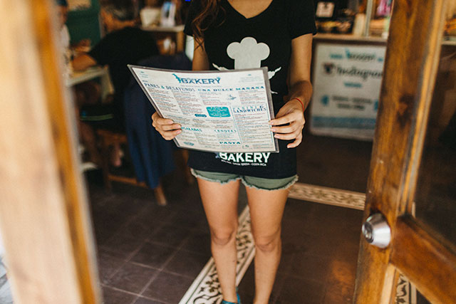 Female employee of The Bakery holding their menu