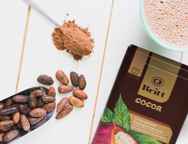 Cafe Britt hot chocolate tin, spoon with powdered cocoa, and scoop with cacao beans