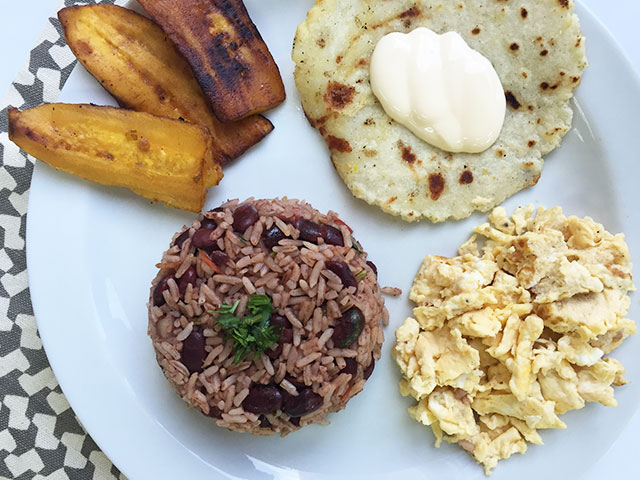 Traditional Costa Rican breakfast: gallo pinto, eggs, tortilla, fried plantains, and sour cream