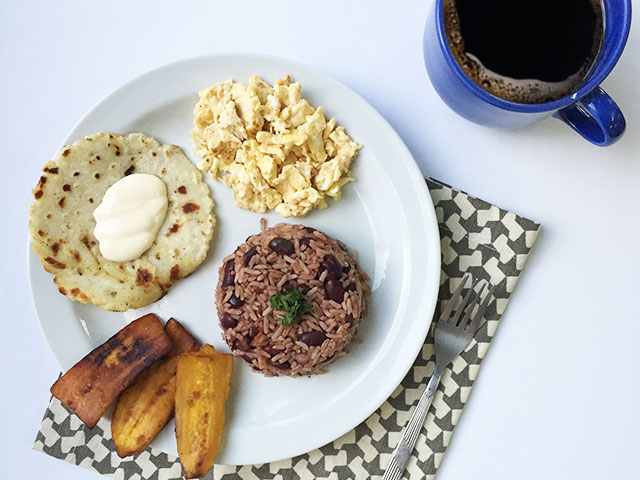 Coffee and traditional Costa Rican breakfast: gallo pinto, eggs, tortilla, fried plantains, and sour cream