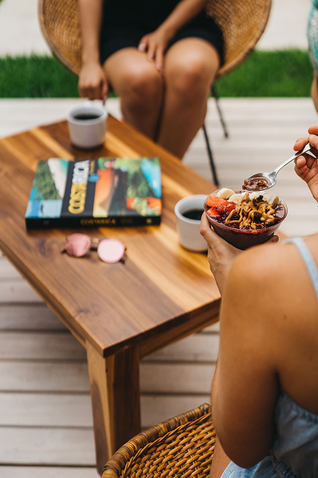 Woman eating acai bowl and woman with coffee cup