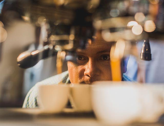 Man watching an espresso shot being prepared