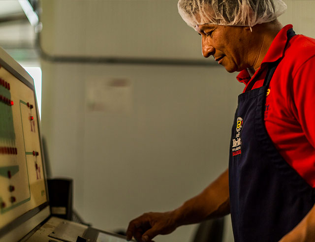 Man in hairnet reviewing a large computer