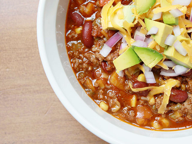 Bowl of chili with cheese, onions, and avocados