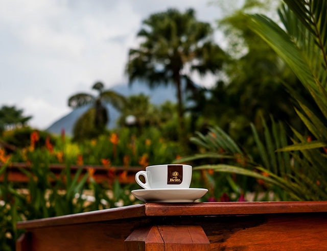 Cafe Britt coffee cup with view of Arenal Volcano behind