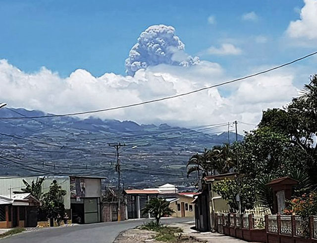 Town with volcano erupting in background