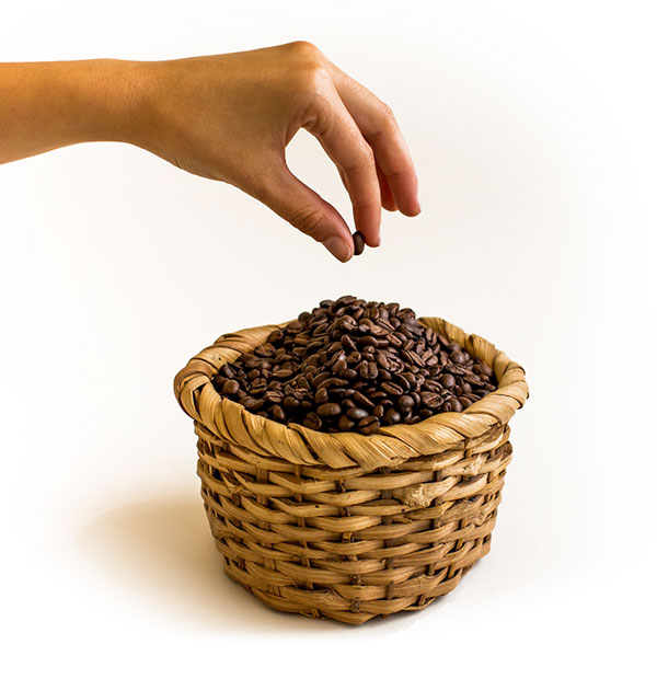 Hand putting a coffee bean in a coffee basket